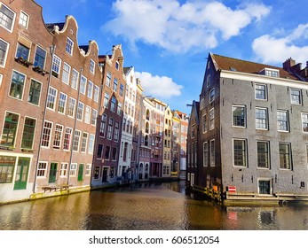 the famous corner in Amsterdam with the beautiful houses alongside the canals by Amsterdam Central Damrak March 2017 Netherlands