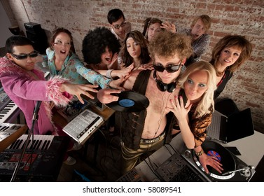 Famous DJ crowded by fans and requests at a party