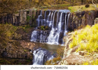 The famous Ebor Falls of the Guy Fawkes River cascades over brown cliffs on Waterfall Way in the New England region of New South Wales (NSW) Australia.