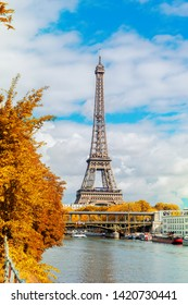 famous Eiffel Tour over Seine river with yellow trees, Paris, France at fall
