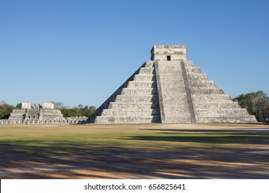 Famous el Castillo Temple of Kukulkan and Temple of the Warriors at Maya ruins of Chichen Itza during late afternoon with clear blue sky, shadows, and no people