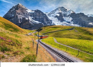 Famous electric red tourist train coming down from the Jungfraujoch station(top of Europe) in Kleine Scheidegg. Eiger North face in background, Grindelwald, Bernese Oberland, Switzerland, Europe
