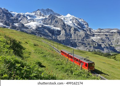 Famous electric red tourist train coming down from the Jungfraujoch station (top of Europe) in Kleine Scheidegg, Bernese Oberland, Switzerland, Europe. Glacier Express.