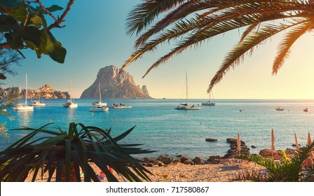 Famous, empty and beautiful Cala d'Hort beach, in summer very popular, sandy coast have a fantastic view of mysterious island of Es Vedra. Moored vessels on bay. Ibiza Island, Balearic Islands. Spain