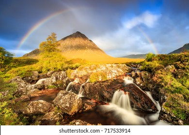 Famous Etive Mor Waterfall with rainbow in the background in Scotland.