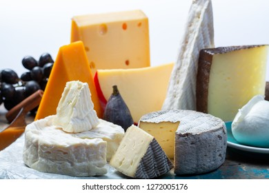 Famous European cheeses in assortment, Dutch red bal Edam and old cheeses with holes, Spanish Manchego cheese, French soft Brie and Camembert, English cheddar and Italian mozzarella buffalo