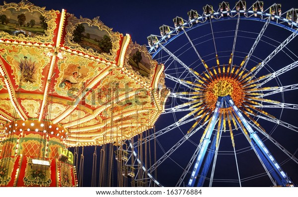 famous ferris wheel and old carousel at the oktoberfest in munich - germany