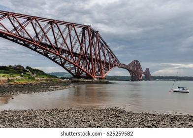 Famous Forth Bridge in Edinburgh, Scotland with a small boat in background.
