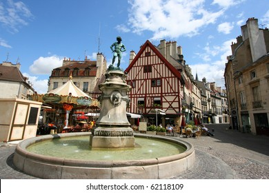 Famous fountain, characteristic houses and colorful carousel in Dijon, Burgundy, France. Place Francois Rude.
