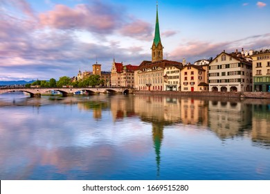 Famous Fraumunster church with its reflections in river Limmat at pink sunrise in Old Town of Zurich, the largest city in Switzerland