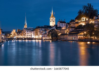 Famous Fraumunster and Church of St Peter with reflections in river Limmat at night in Old Town of Zurich, the largest city in Switzerland