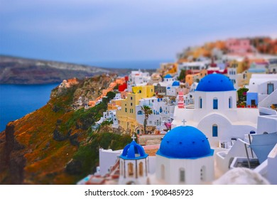 Famous greek iconic selfie spot tourist destination Oia village with traditional white houses and church in Santorini island on sunset in twilight, Greece. Toy camera tilt shift miniature effect