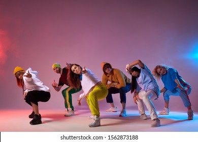 Famous group finish dancing , sitting on squats, looking at audience, making come alone gesture, expressing cheerfulness, dressed in sportswear, hip hop, street dance , break dance concept