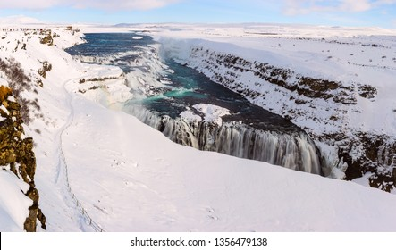 Famous Gullfoss (Gulfoss) Waterfall situated on the Golden Circle in Iceland. Snowy Iselandic landscape with emerald color water cascades of river Olfusa.