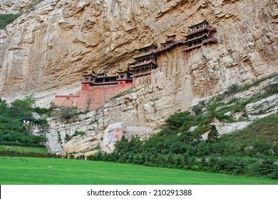 Famous hanging monastery in Shanxi Province near Datong, China, viewed from distance, stylized and filtered to resemble an oil painting.
