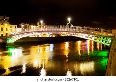 Famous 'Ha'penny Bridge' in Dublin over colorful Liffey river at night