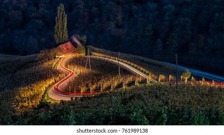 Famous Heart shaped wine road in Slovenia in autumn, Heart form - Herzerl Strase with a couple, holding hands and walking in sunset, surrounded with vineyards in autumn; Dreisiebner