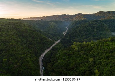 A famous highway called Los Chorros, in the outskirts of San Salvador stretching across a mountainous terrain with light traffic early in the morning.