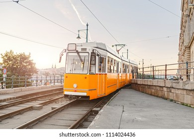 Famous historic yellow tram riding down city street in Budapest