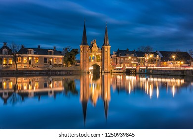 The famous historical 'Waterpoort' in the city of Sneek at night with reflections in the canal - Sneek, Friesland, The Netherlands