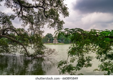 The famous hoan kiem lake in hanoi. with a magnificient tree in the foreground and the pagoda in the background