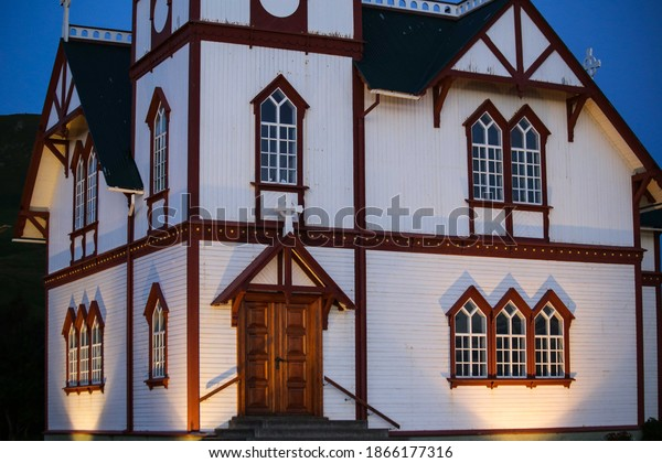 The famous Husavik Church with outdoor lights aglow in the evening in early autumn in Husavik, northern Iceland