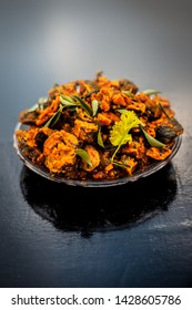 Famous Indian & Gujarati snack dish in a glass plate on wooden surface i.e. Patra or paatra consisting of mainly Colocasia esculenta or arbi ke pan or elephant ear leaves and spices.Vertical shot.