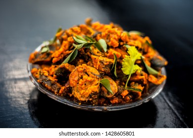 Famous Indian & Gujarati snack dish in a glass plate on wooden surface i.e. Patra or paatra consisting of mainly Colocasia esculenta or arbi ke pan or elephant ear leaves and spices.