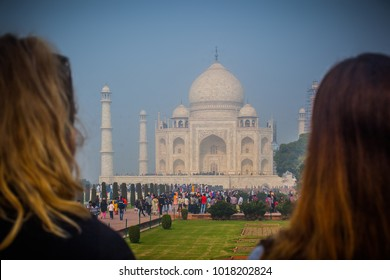 Famous indian tomb Taj Mahal being viewed with two long haired women tourists standing in the foreground.