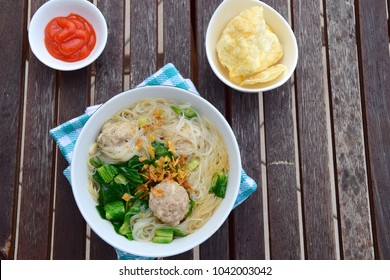 Famous Indonesian food, Bakso or Meatballs with kai lan and rice vermicelli sprinkle with fried shallot served with emping and sambal