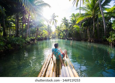 Famous instagrammed leaning palm tree at Maasin River in Siargao, Philippines - People having fun swinging on a coconut tree in the jungle