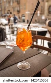 Famous Italian summer aperitif. Beautiful Aperol spritz cocktail. Bright orange drink on the table. Milan, Italy.