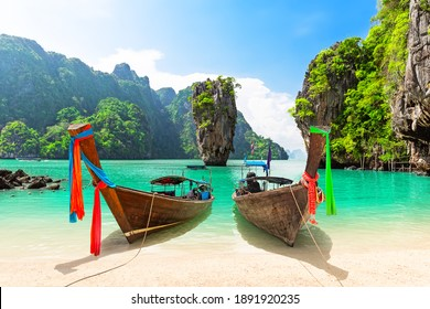 Famous James Bond island near Phuket in Thailand. Travel photo of James Bond island with thai traditional wooden longtail boat and beautiful sand beach in Phang Nga bay, Thailand.