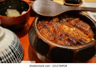 Famous Japanese food, Hitsumabashi eel, Famous dish in Nagoya Japan. Unadon or Grill eel on rice served in wooden bowl with rice ladle for divide the bowl's contents into four servings.