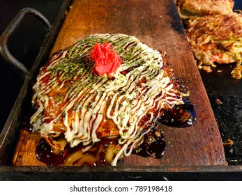 The famous Japanese food in Osaka, named Okonomiyaki. the Japanese style fried pancake on wooden plate topping with vegetables, mayonnaise and red ginger.