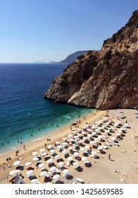 """The famous """"Kaputas Beach"""". Excellent nature and sea. People entering the sea and the beach. Beach umbrellas and sunbeds. View of the beach from above. Kas region, Antalya, Turkey. June 2, 2019."""