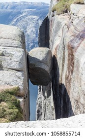 Famous Kjeragbolten boulder stuck between two granite cliffs on Kjerag mountain, a famous hike in Rogaland, Norway
