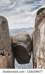 Famous Kjeragbolten boulder stuck between two granite cliffs on Kjerag mountain, Norway
