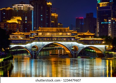 Famous landmark of Chengdu - Anshun bridge over Jin River illuminated at night with modern skyscrapers in background, Chengdu, Sichuan , China