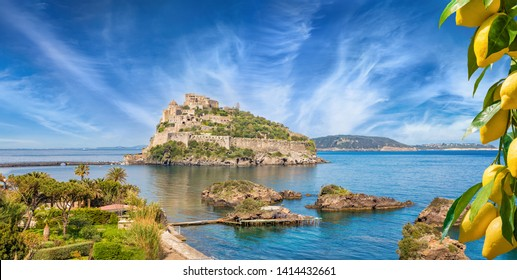 Famous landmark and tourist destination Aragonese Castle or Castello Aragonese located near Ischia Island, Italy. Ripe yellow lemons in foreground.