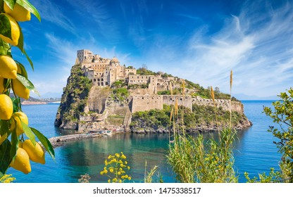 Famous landmark and tourist destination Aragonese Castle or Castello Aragonese located near Ischia Island, Italy. Bunches of fresh yellow ripe lemons in foreground.