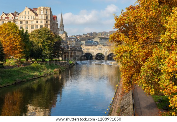 The famous landmarks of Pulteney Weir and Pulteney Bridge surrounded by vibrant autumnal trees on the River Avon in Bath, UK.