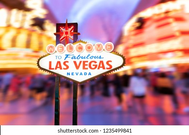 Famous Las Vegas sign at night with Las Vegas Cityscape blur background.