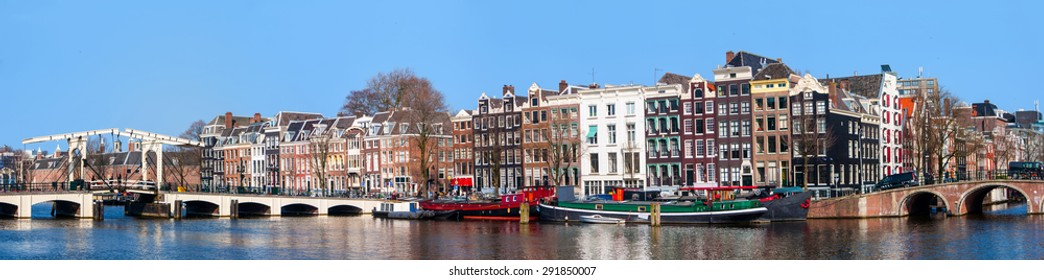 Famous Magere Brug (Skinny Bridge) in Amsterdam, Netherlands with historical buildings, many cafes and restaurants. Panoramic view