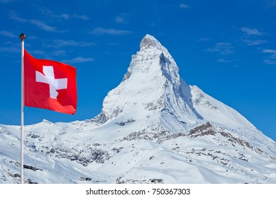 Famous Matterhorn with flag of switzerland on blue sky