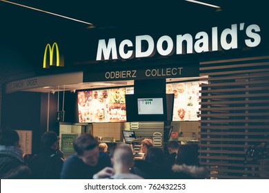 Famous McDonald's restaurant, Poland - Nowy Sacz - November 25, 2017. Staff prepares meals for release and above them the illuminated menu with food sets.