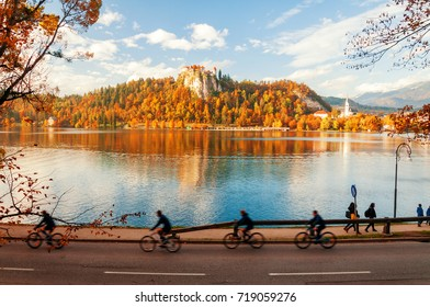 Famous medieval castle on the top of rock above lake with reflection in water and bicyclists in motion on foreground. Location place: Blejski grad, Bled, Slovenia. Beautiful sunny autumn scenery.