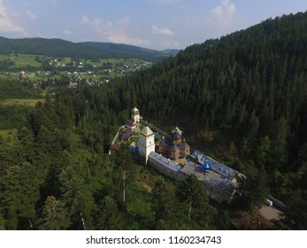 The famous medieval fortified Orthodox Maniava Skete monastery, aerial summer view. Skete is located deep in the forest on outskirts of Maniava village in the Carpathian mountains, Western Ukraine