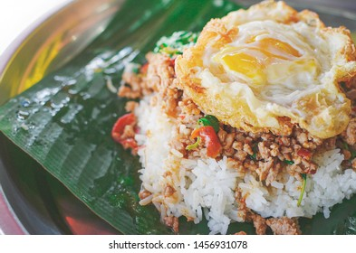 Famous menu of Thai food, pad kra pao, spicy fried mince pork with basil leaves add topping with fried egg. Close up view.