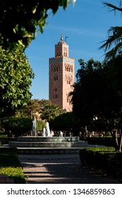 The famous minaret of Koutoubia Mosque as seen through palm tree leaves in Parc Lalla Hasna during a spring morning (Marrakesh, Morocco, Africa)